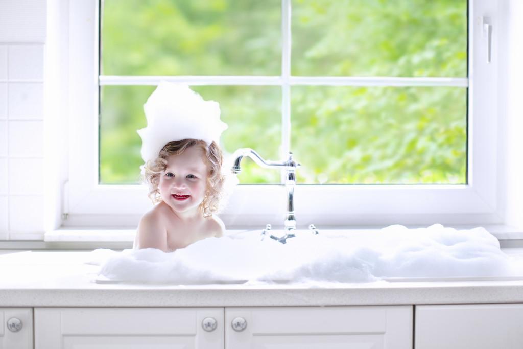 Baby bathing in tap water